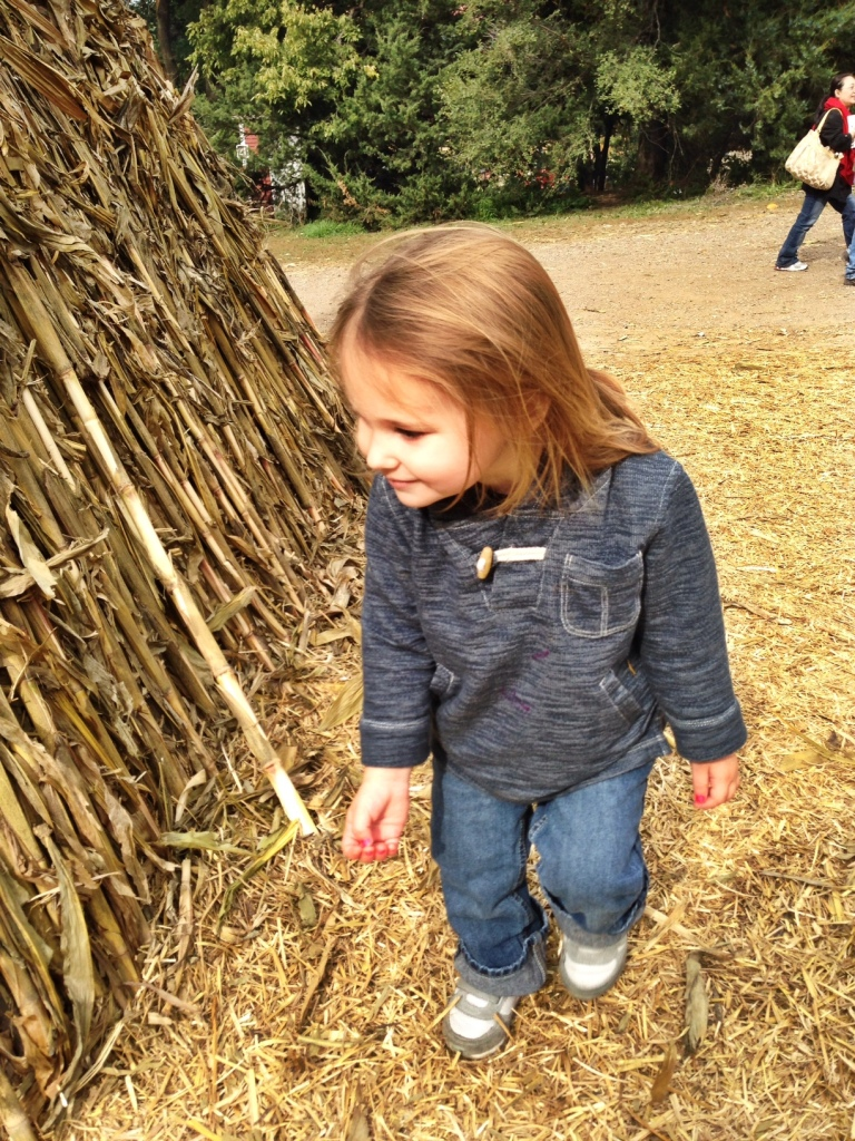 Baby by a corn stalk teepee